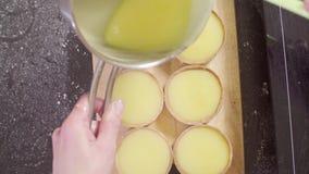 Handen van een gestremde melk van de banketbakkers gietende citroen in tartlets stock video