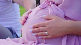 Handen van een jong echtpaar op de grote buik van een zwangere vrouw Het wachten op het kind stock video