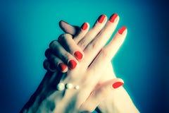 Handen van een jong meisje met rode spijkers en dalingen van room Close-up op een blauwe achtergrond Wijnoogst, grunge retro stij stock foto's