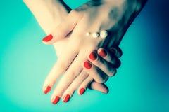 Handen van een jong meisje met rode spijkers en dalingen van roomclose-up royalty-vrije stock fotografie