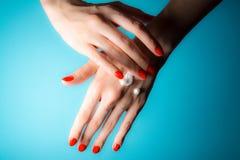 Handen van een jong meisje met rode spijkers en dalingen van roomclose-up op een blauw royalty-vrije stock afbeelding