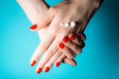 Handen van een jong meisje met rode spijkers en dalingen van roomclose-up op een blauw stock afbeelding