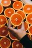 Handen van een jonge vrouw die een rode grapefruit houden Gezond voedselconcept stock afbeelding