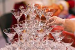 Handen van een kelner die piramide van glazen voor dranken, wijn, champagne, feestelijke stemming, viering opmaakt Stock Afbeeldingen