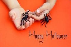 Handen van een kind die met zwart rubberspinnenspeelgoed spelen op oranje document achtergrond Het concept van Halloween oktober stock foto's