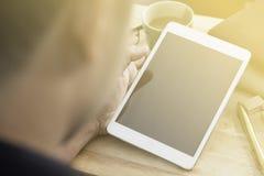 Handen van een leeg de tabletapparaat van de mensenholding over een houten werkruimtelijst Stock Foto's
