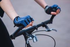 Handen van een meisje die in sporten blauw-zwarte handschoenen op houden Royalty-vrije Stock Foto's