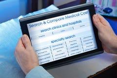 Handen van een mens die een website van online gezondheidsdienst binnen raadplegen Stock Afbeelding