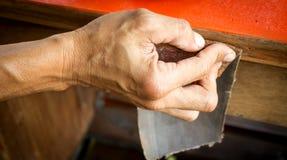 Handen van een mens met schuurpapier stock afbeelding