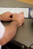 Handen van een mens op een Desktop naast een klembord Royalty-vrije Stock Foto