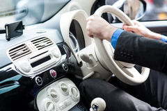 Handen van een mens op stuurwiel van een auto Royalty-vrije Stock Foto's