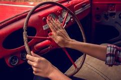 Handen van een mooi meisje die het stuurwiel van een oude rode auto houden stock fotografie