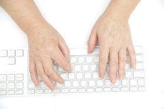 Handen van een oud wijfje dat op het toetsenbord typt Stock Afbeelding