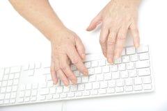 Handen van een oud wijfje dat op het toetsenbord typt Stock Fotografie