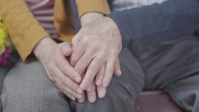 Handen van een oude vrouw die de hand van de oude mens houden De handen van rijpe mensen sluiten omhoog Teder verhoudings volwass stock footage