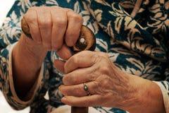 Handen van een oude vrouw die op een stok leunt Stock Fotografie