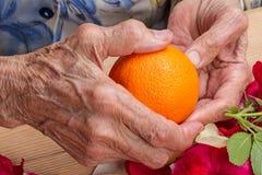 Handen van een oude vrouw met een sinaasappel stock foto