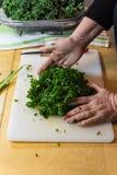 Handen van een vrouw die samen vers gehakte en gemasseerde boerenkoolbladeren op een scherpe raad verzamelen Stock Afbeelding
