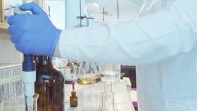 Handen van een wetenschapper die oplossing titreren stock footage