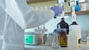 Handen van een wetenschapper die een reagens laten vallen in flessen stock video