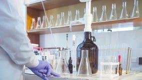 Handen van een wetenschapper het gieten oplossing in flessen stock video