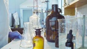 Handen van een wetenschapper het gieten oplossing in flessen stock footage