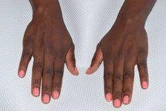 Handen van een zwarte Afrikaanse vrouw met roze nagellak op witte achtergrond Stock Foto's