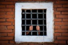 Handen van gevangene achter de bars, kleur royalty-vrije stock afbeelding