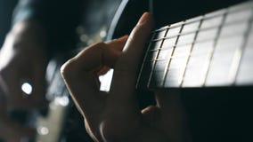 Handen van het mannelijke musicus spelen bij elektrische gitaar De wapensspelen van mensen solo van rock Sluit omhoog vingers van stock video