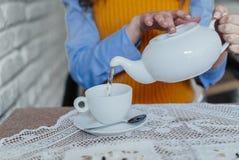 Handen van het meisje dat thee giet Stock Afbeelding