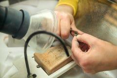 Handen van het metaal mondelinge prothese van de tandtechnicusverwerking stock foto's