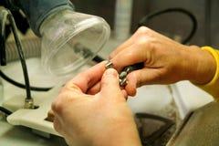 Handen van het metaal mondelinge prothese van de tandtechnicusverwerking stock afbeelding