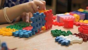 Handen van het onbekende kind spelen met de bouw van uitrusting stock footage