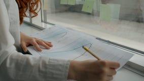 Handen van het vrouwelijke financiële analitische werken aan document grafieken dichtbij het bureauvenster stock videobeelden