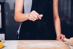 Handen van het wijfje die van de bakkersvrouw het bestrooien van bloemdeeg maken royalty-vrije stock foto's