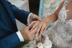 Handen van huwelijkspaar die gouden ringen zetten aan vinger van elkaar royalty-vrije stock afbeelding