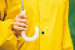 Handen van jong meisje in de gele paraplu van de regenjasholding Het concept van de de herfstdag royalty-vrije stock afbeelding