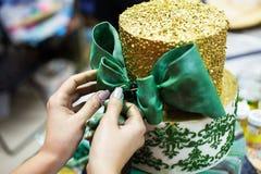 Handen van jonge dame die cake met vlinderdas verfraaien royalty-vrije stock foto