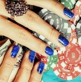 Handen van jonge Kaukasische vrouw met blauwe manicure bij casino tabl Royalty-vrije Stock Foto's
