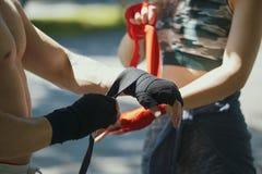 Handen van jonge man en vrouwen verpakkende handen met verbanden voor training in de zomerdag Stock Foto