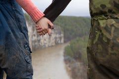 Handen van jonge paarwandelaars die zich op de rand van een klip over de bergrivier bevinden Royalty-vrije Stock Afbeeldingen