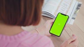 Handen van jonge vrouw en een gadget, een tijdschrift op de achtergrond stock video