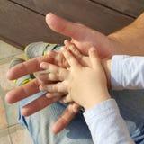 Handen van jongen op hand van de mens stock fotografie