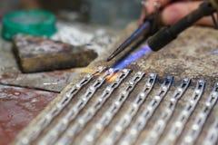 Handen van juwelier bij het werk het zilveren solderen Stock Foto