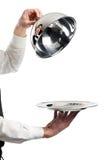 Handen van kelner met glazen kapdeksel