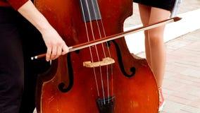 Handen van kerel die de viool in straat en benen og meisje spelen die rode keds dichtbij dragen stock video