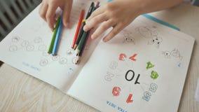 Handen van kinderen die met potloden in kleuterschool trekken Close-up stock footage
