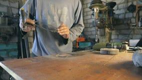 Handen van mechanisch greepdetail tijdens het werkproces De hersteller controleert het detail na werkt De mensenwerken in zijn ga stock video