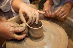 Handen van meester die pot op het wiel van de pottenbakker creërt Stock Afbeeldingen