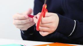 Handen van meisjes scherpe bloem van gekleurd document voor ambachten stock videobeelden